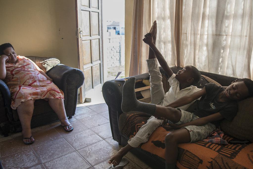 Hlumelo macht zu Hause  einige Dehnübungen, bevor seine Ballettstunde beginnt. Seine Tante Princess passt auf die drei Brüder auf, während ihre Mutter arbeitet.