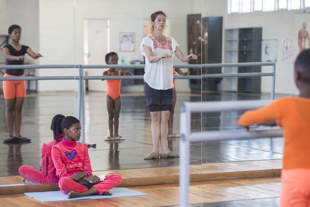 Obwohl Similise krank ist, wollte sie unbedingt zur Ballettstunde gehen. Weil sie nicht tanzen kann, sitzt sie vorne und sieht der Klasse zu.